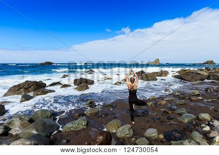 Summer yoga session on beautiful Playa de Roque de Las Bodegas with giant rock and high waves - tropical Tenerife island, Canary in Spain. Vriksha-asana, tree pose