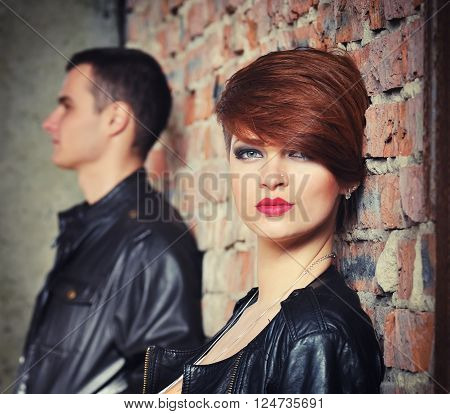 Young couple near the brick wall. Focus on girl