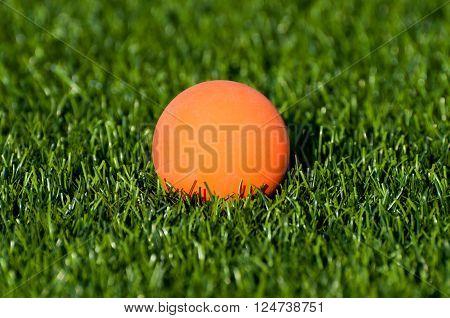 An orange lacrosse ball on artificial turf.