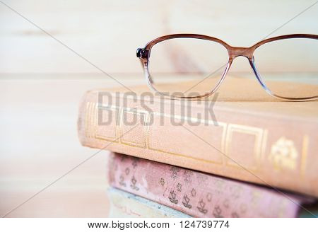 Composition with glasses and books, on table, on light background close up