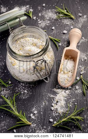 Sea salt with rosemary and lemon zest on black slate board. Top view.