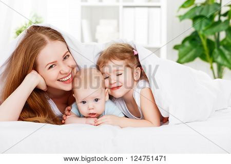 happy family mother and two children son and daughter in bed playing under blanket