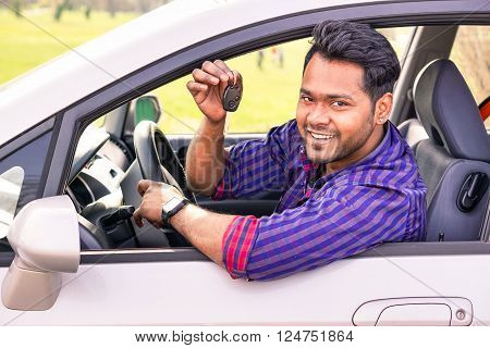 Young indian happy man inside new car - Cheerful asian man showing car key outdoor - Successful businessman inside automobile looking at camera and smiling - Concept of happiness and success