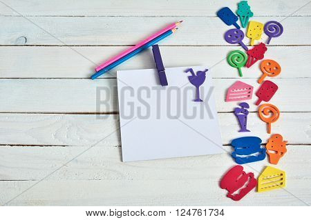 Notebook with  pencil on wooden background and fanny cartoon food