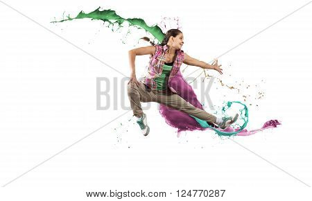 Young female dancer in jump on white background with colorful paint plashes