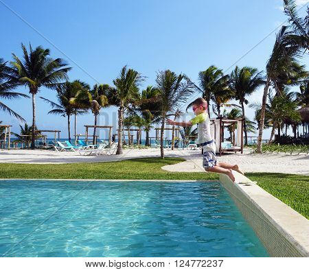 Picture of a young boy jumping in a pool in Mexico.