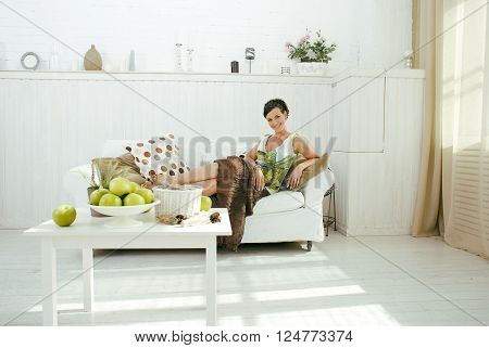 young pretty real brunette woman at home laying on sofa, lifesyle people concept, bright white interior