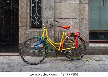 AMSTERDAM, NETHERLANDS - JULY 07, 2015: Colorful bicycle leaning against wall in Amsterdam - most bicycle-friendly capital city in the world where over 60% of trips are made by bike.