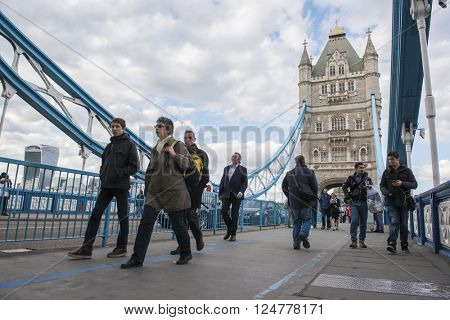 LONDON, UK - APRIL 05 2016: Commuters crossing Tower Bridge during rush hour. Tower Bridge links the South of River Thames to the City area.