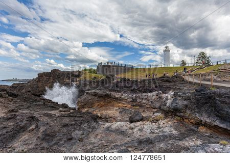 KIAMA, AUSTRALIA - MAR 30 2016: Kiama Lighthouse with water spraying out of the blowhole, Sydney, NSW, Australia