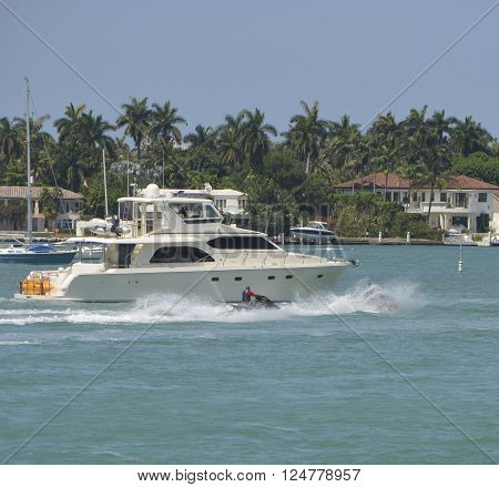 Small motor yacht and jet skiers against a tropical background of upscale homes on an island in the city of miami beach,florida ** Note: Soft Focus at 100%, best at smaller sizes