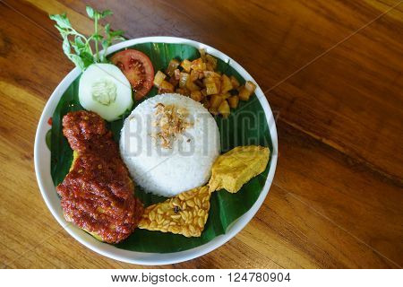 A set of 'Ayam Penyet' on table setup. Ayam penyet is Indonesian cuisine. fried chicken dish consisting of fried chicken served with sambal slices of cucumbers tempe and rice.