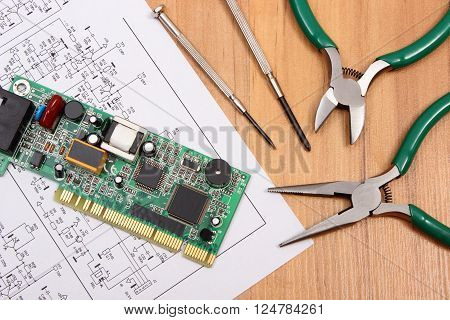 Printed circuit board with electrical components precision tools and construction drawing of electronics on wooden board drawings and tools for engineer jobs technology