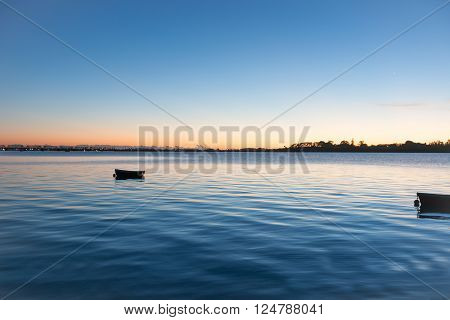 Sunrise across bay with small dinghy blue tones with orange around horizon ** Note: Soft Focus at 100%, best at smaller sizes