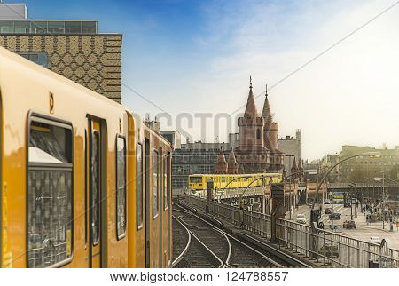 Panoramic view of Berliner U-Bahn trains with Oberbaumbridge in the background in golden evening light at sunset, Berlin Friedrichshain-Kreuzberg, Germany