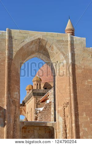 Part of Ishak Pasha Palace against blue sky background. Stone decorations are seen.