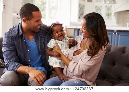 Happy parents with baby girl standing on mumâ??s knee