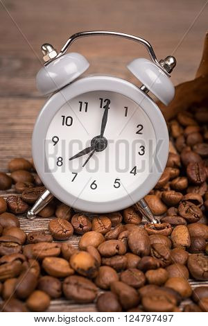 vintage alarm clock and coffee beans on wooden table ** Note: Shallow depth of field