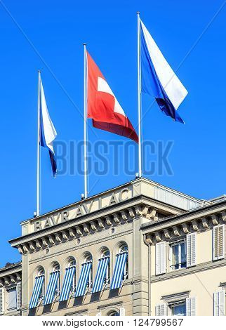 Zurich, Switzerland - 3 August, 2015: flags of Zurich and Switzerland on the top of the Baur au Lac Hotel building. The Baur au Lac is a luxury hotel located on the Talstrasse street in Zurich, Switzerland.