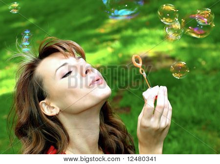 attractive young girl inflating vivid soap bubbles outdoor