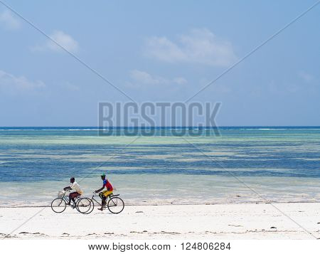 PAJE ZANZIBAR - MARCH 30 2016: Local people biking on the beach in Zanzibar Tanzania.