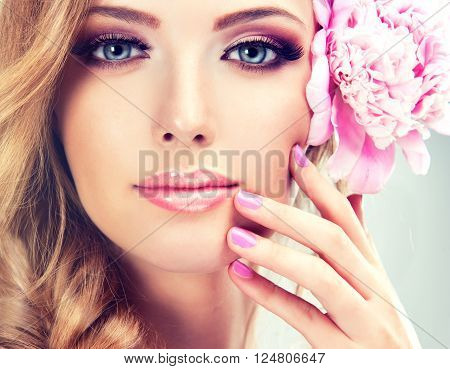 Beautiful model girl  with a pigtail ,     flower barrette .  Hairstyle braid  with pink  peony  .  Pink Manicure nails