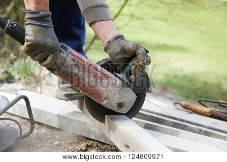 Construction worker cutting a reinforced concrete pillar for installation with professional machine. Construction business do-it-yourself dirty and dangerous work around the house concept.