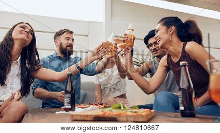 Group of friends toasting beers in a party while sitting around table. Multiracial friends hanging out on rooftop enjoying party.
