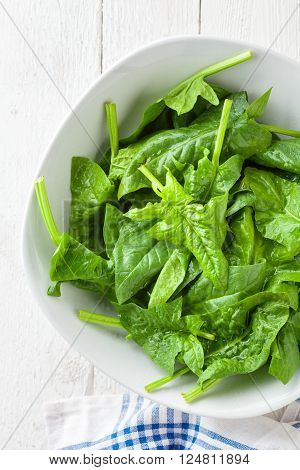 Raw Spinach in a White Bowl on White Wood