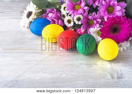 an Easter ornament for background of colorful eggs and flowers on a white background wooden