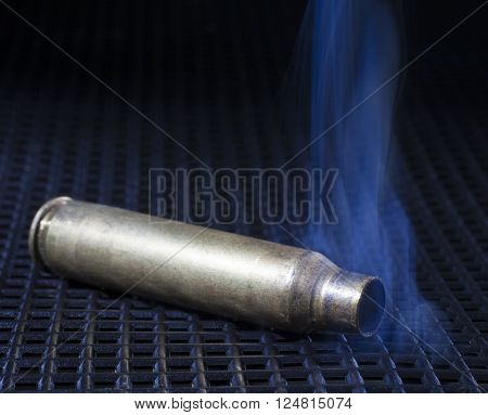 Emtpy brass from a rifle on a black grate with smoke