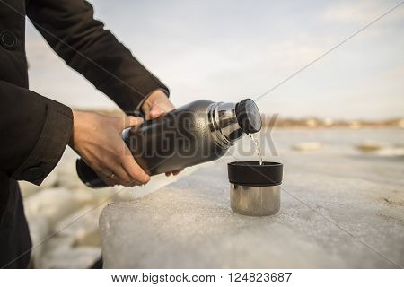 Man pours hot tea from a thermos into a cup which stands on an ice floe on the river bank in the spring sunny day
