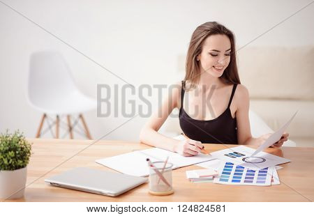 Much work to do. Cheerful vivacious charming girl sitting at the table and holding pencil while working with papers