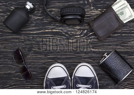 Men's accessories: wallet, headphones, sunglasses, perfume, flask and  sneakers on wooden background