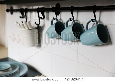 Blue cups is located on the pure white wall in the kitchen above the owen. closed to cups are located some other applience needed for cooking ** Note: Shallow depth of field