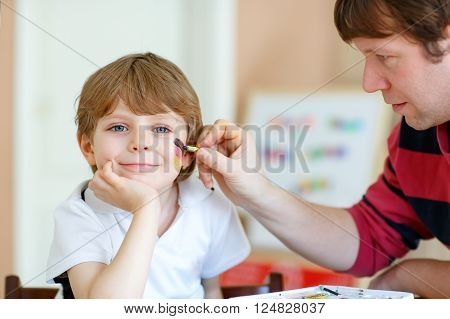 Young dad painting flag on face of little son for football or soccer game. Kid boy fan happy about game of team in champions league. Selective focus