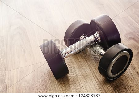 Dumbbells on wooden floor in gym Vintage tone