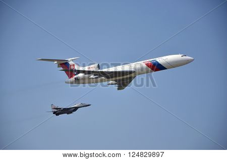 Sliac Slovakia - August 27 2011: Flight display of jet airliner Tupolev Tu-154M (serial number: OM-BYO) escorted by jet air fighter MiG-29 part of Slovak Air Force during air show