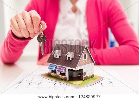Female house agent holding keyring of rented house.