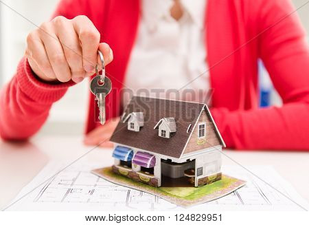 Young female makler holding key of new apartment. Real estate rent and sale concept. Shallow depth of field.