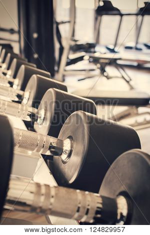 row of dumbbells in sport club Gym interior Vintage tone