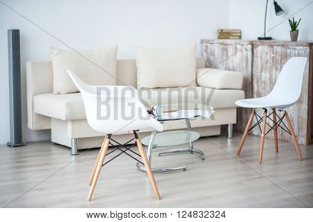 Smart space. View of white furniture specious room with chairs and sofa