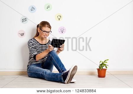 Happy girl sitting on the floor at home using tablet pc for online chatting or shopping. Young smiling female relaxing, surfing internet in her room.