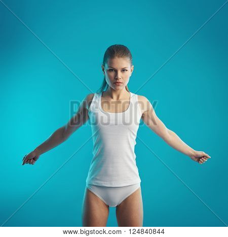 Body rehabilitation. Young woman doing stretching exercise for arms and spine. Muscles recovery concept.