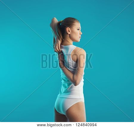 Back rehabilitation after trauma. Young slim female in cotton underwear stretching arms and spine.