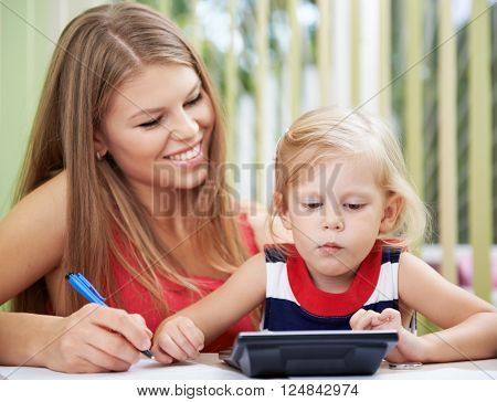 Concentrated girl calculating family bills sitting at the desk with her mom. Budget planning concept.