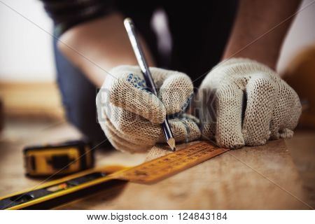 Close-up of craftsman hands in protective gloves measuring wooden plank with ruler and pencil. Woodwork and renovation concept.