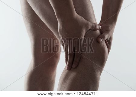 Closeup of young male massaging his sore knee. Joint disease treatment.