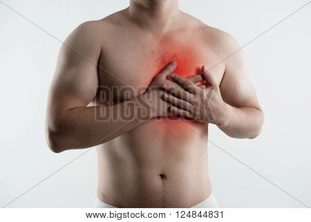 Heart ache and attack. Closeup of male torso with red point on his painful chest.