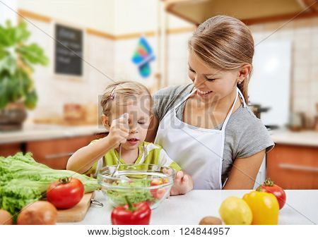 Happy mother and her little daughter preparing meal together. Young woman with baby girl cooking salad in cuisine room.